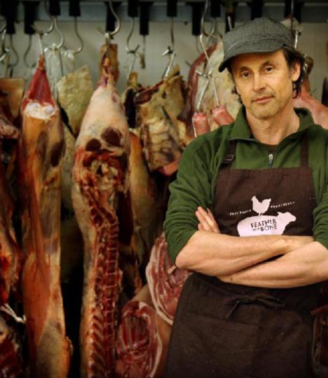 Butcher standing in front of carcasses