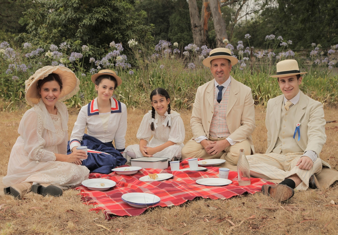Family dressed in period costume seated on picnic rug.