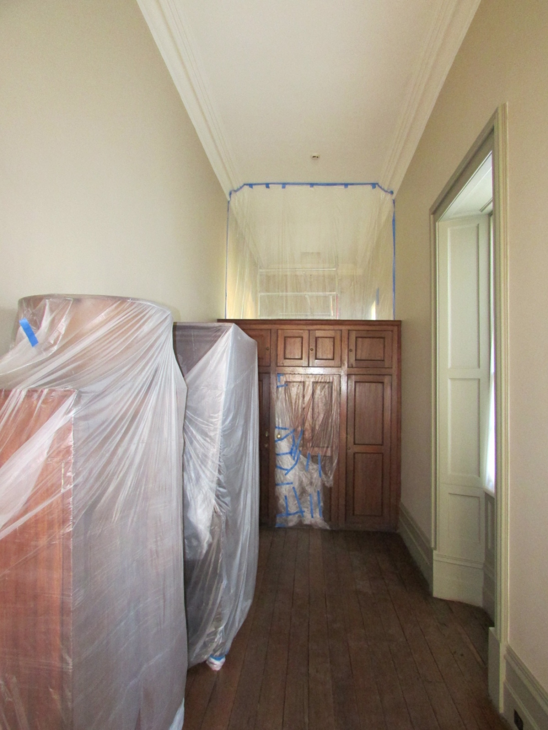Looking into a narrow room with protective cloths up for repair work.
