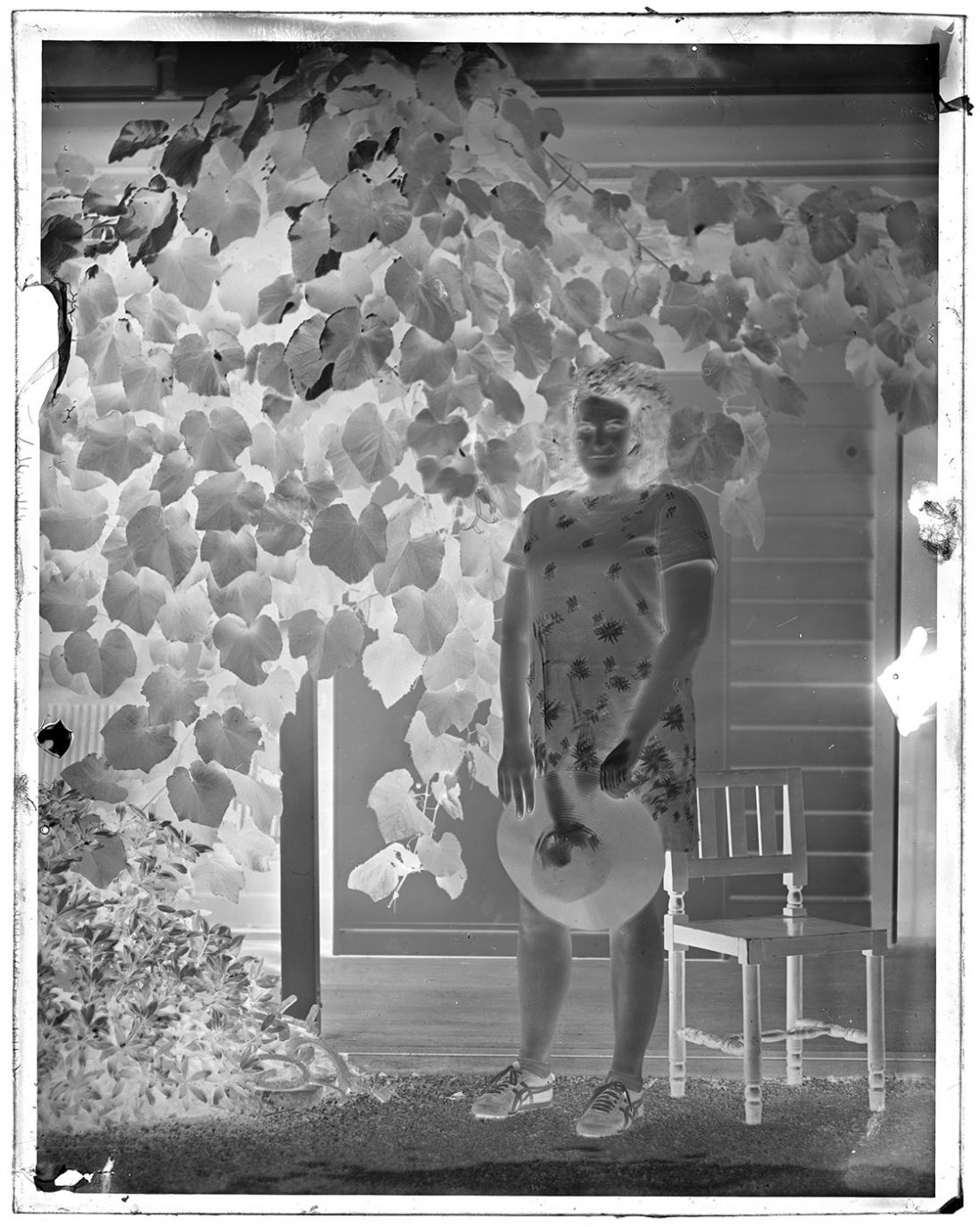 Black and white negative of woman standing in garden.