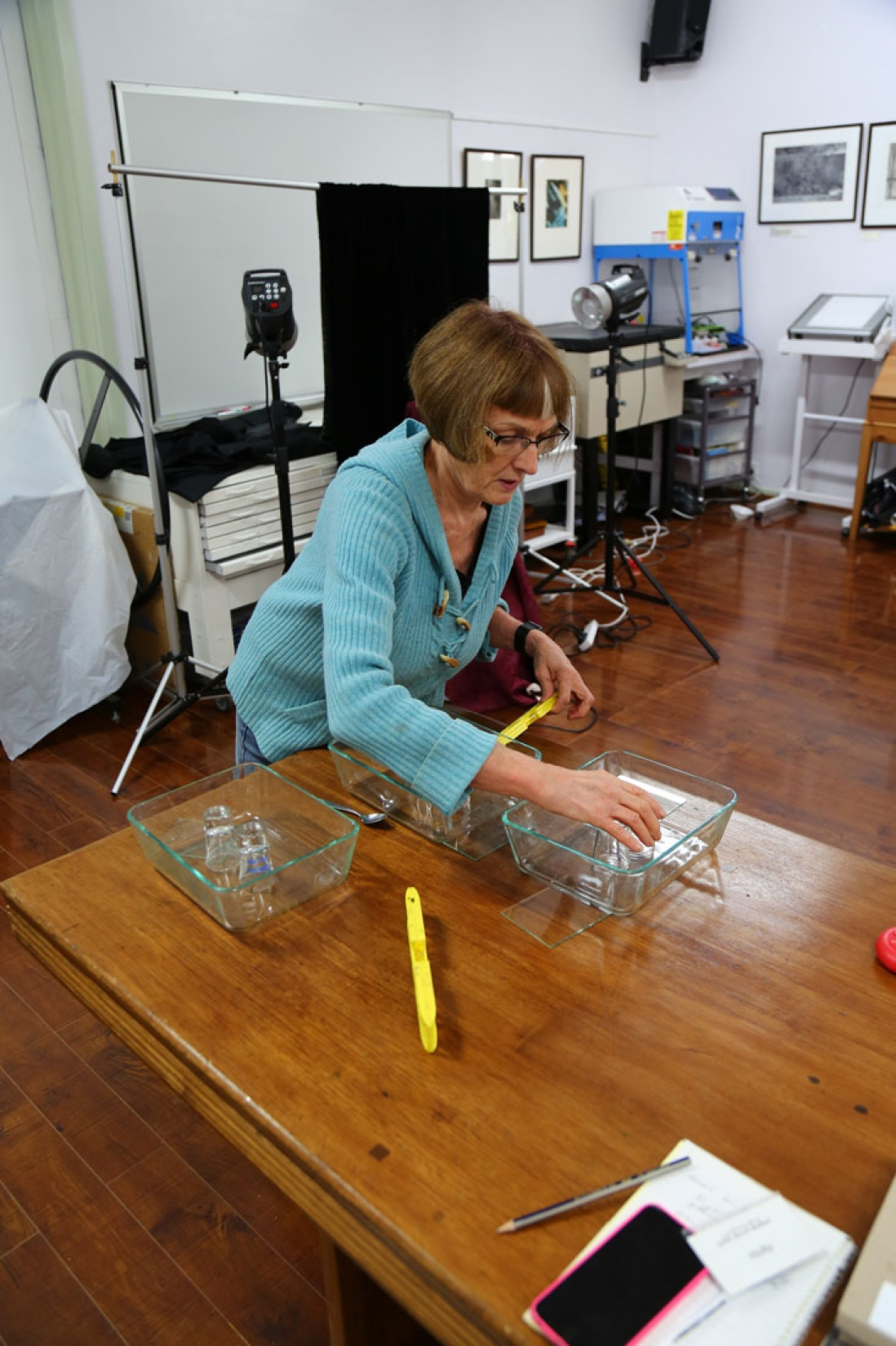 Woman in blue coat working on glass plate at large wooden benchtop.