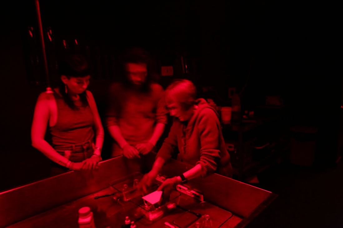 Group in red-lit darkroom working with glass plates and emulsion.