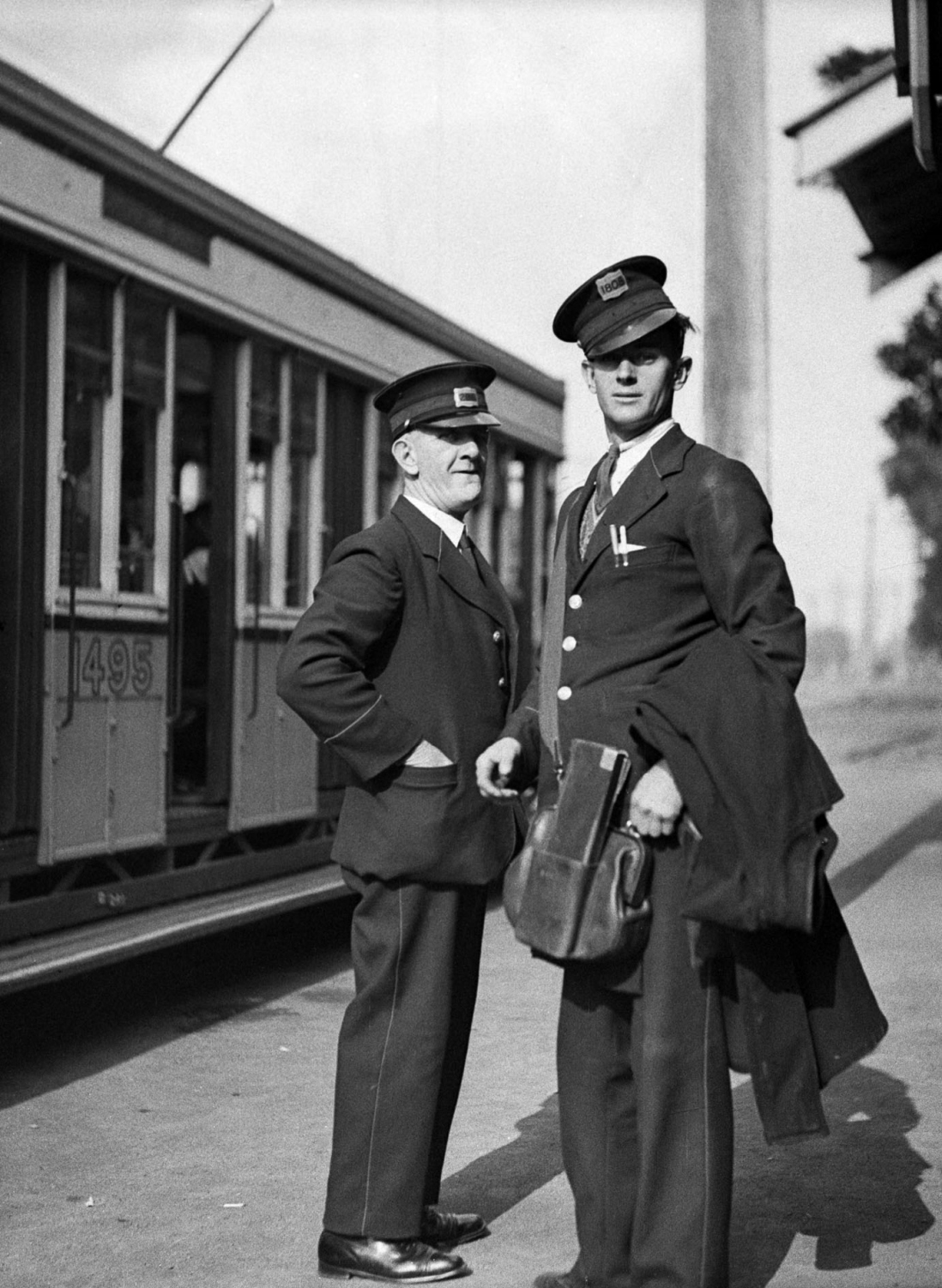 Two uniformed tram way men stand on the street beside a tram. One carries leather bag on his shoulder.