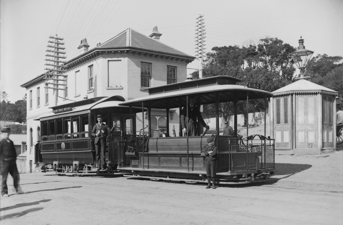 double carriage cable tram on the strret outside a Victorian building.