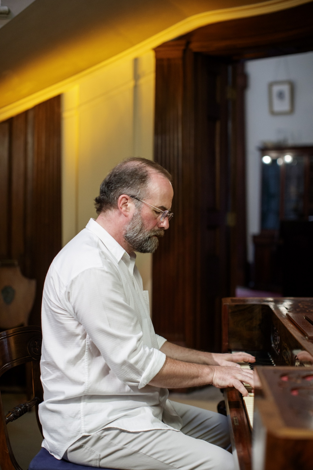 Ian Blake, composer and performer, playing piano in the saloon at Elizabeth Bay House