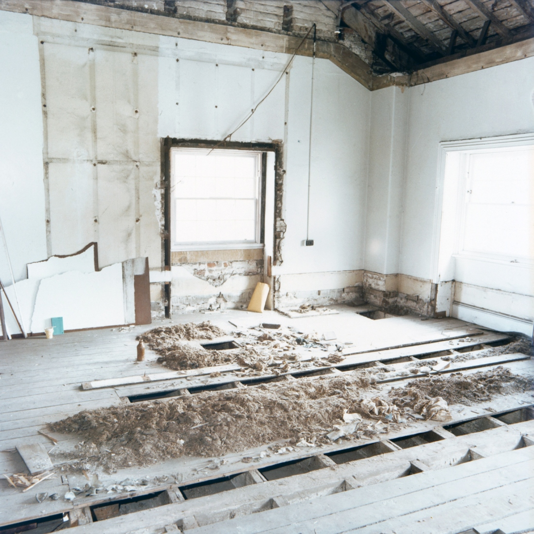 Room with wooden floorboards lifted in centre, with piles of extracted materials.