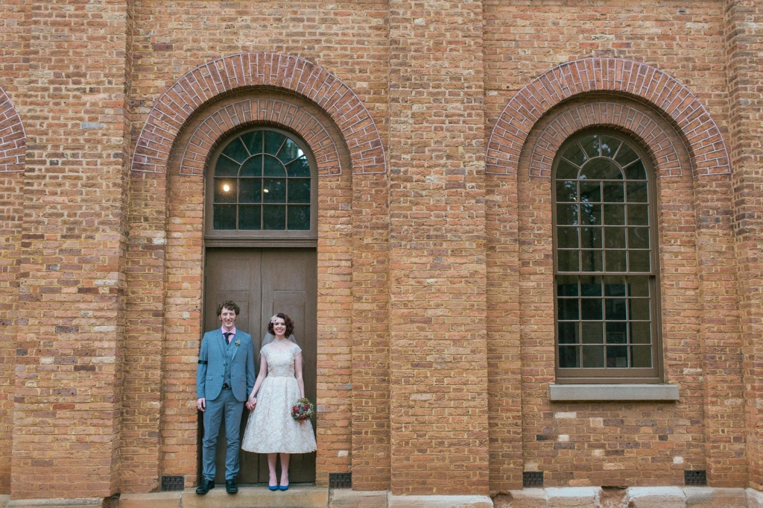 Man and woman standing in arched doorway of brick building.
