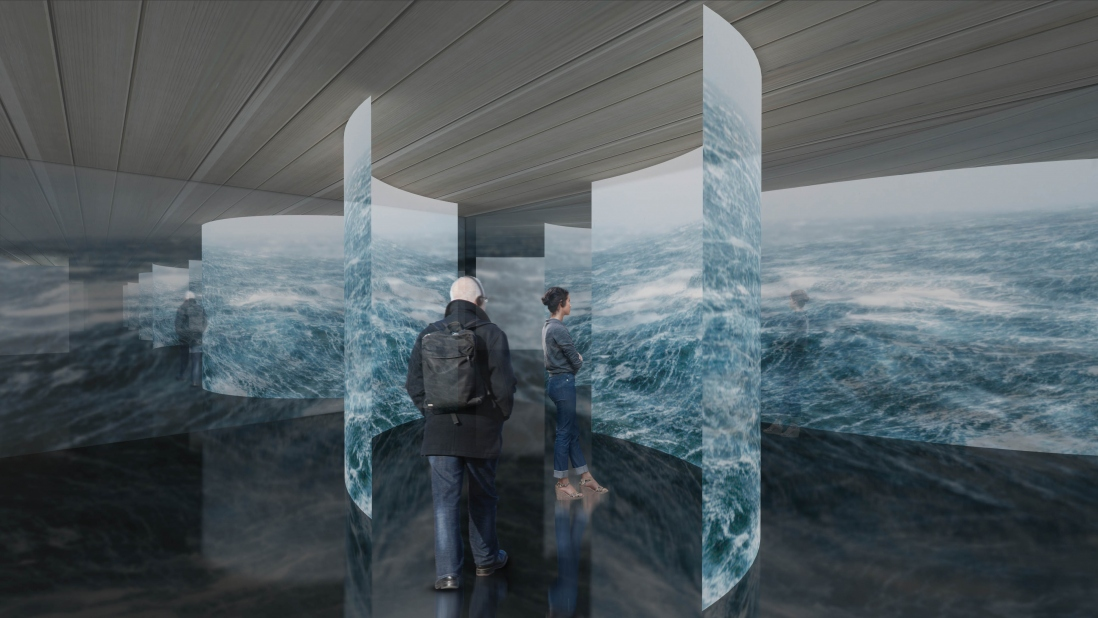 Large projection scrims hang in a gallery showing images of the ocean.