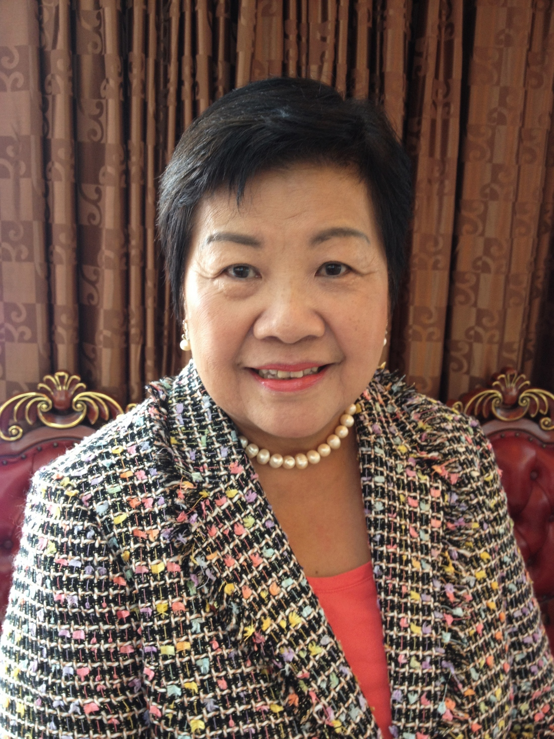 Photo of Helen wearing patterned jacket and pearl necklace.
