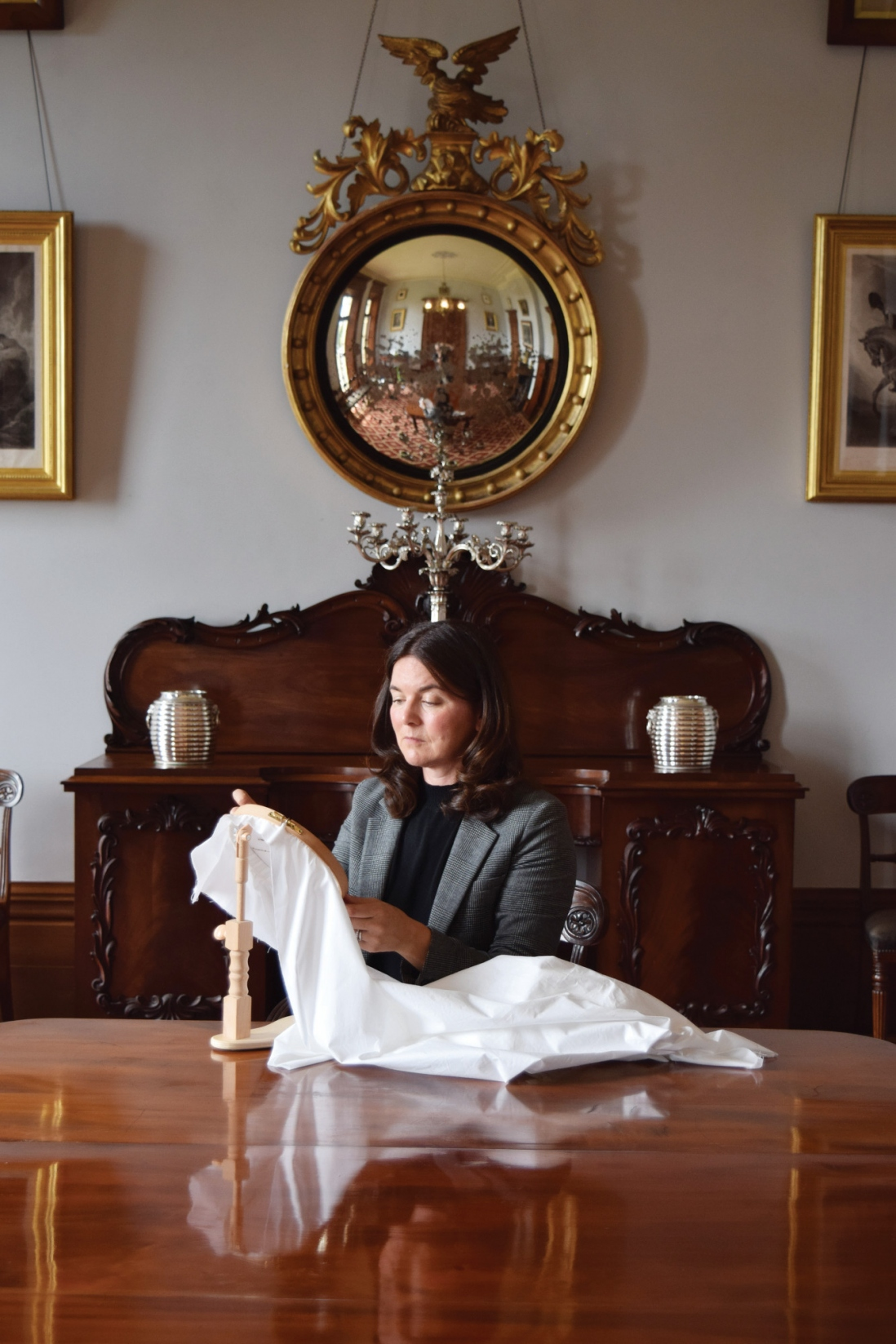 Woman seated at table holding up white fabric, with circular mirror and sideboard behind her.