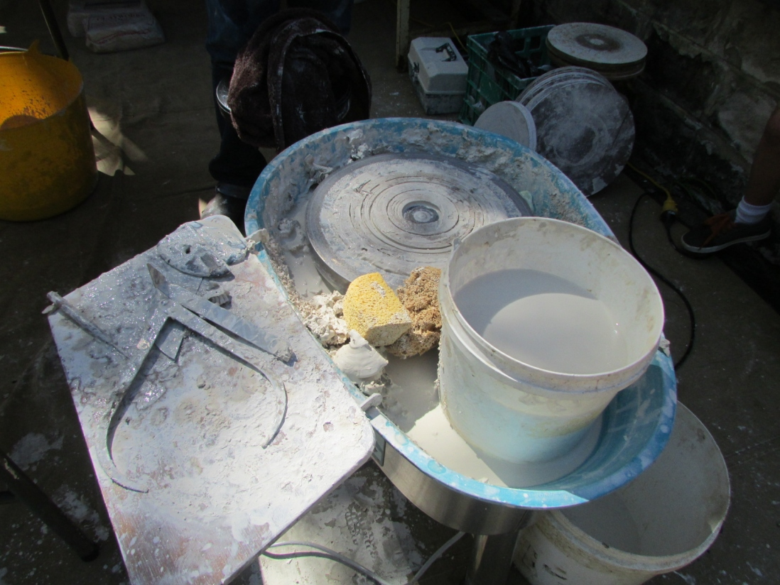 muddy potter's wheel with plastic buckets and callipers