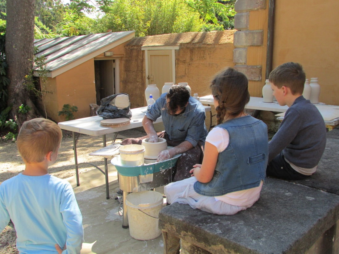 Visitors watch Andrei Davidoff at work on potter's wheel in yellow painted courtyard