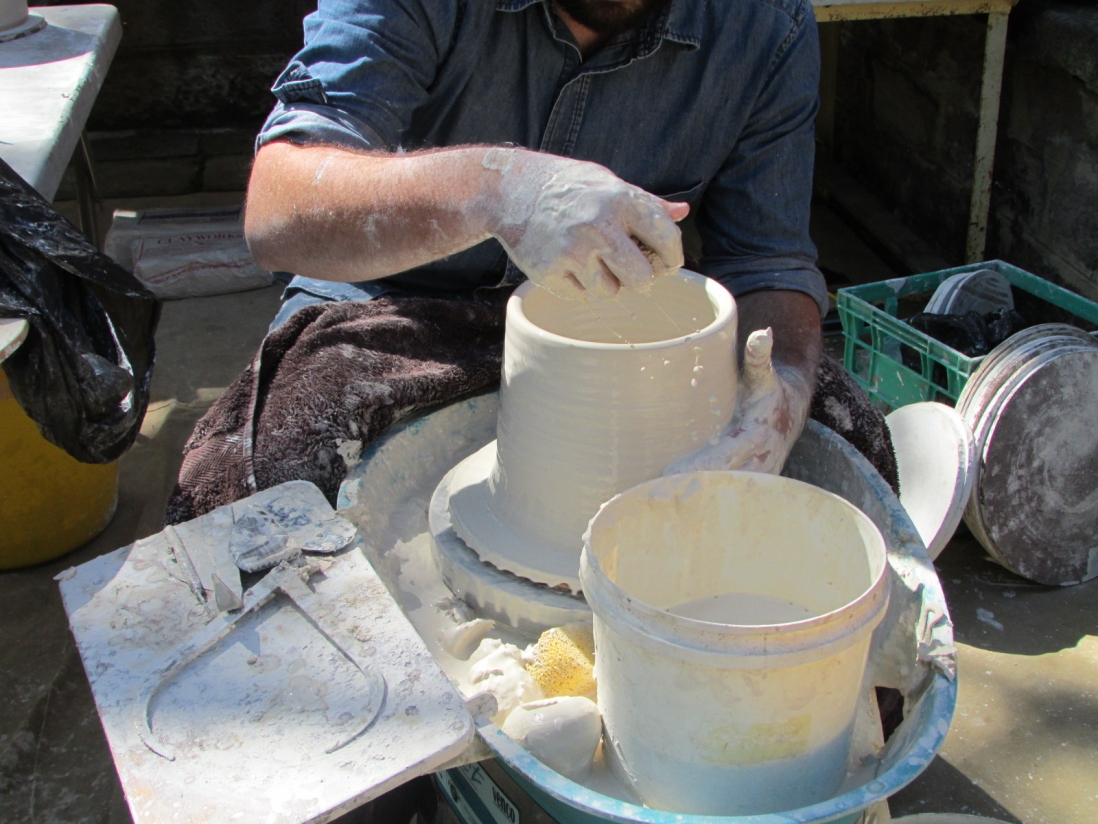 a white cylindrical ceramic vessel on a potter's wheel is almost complete
