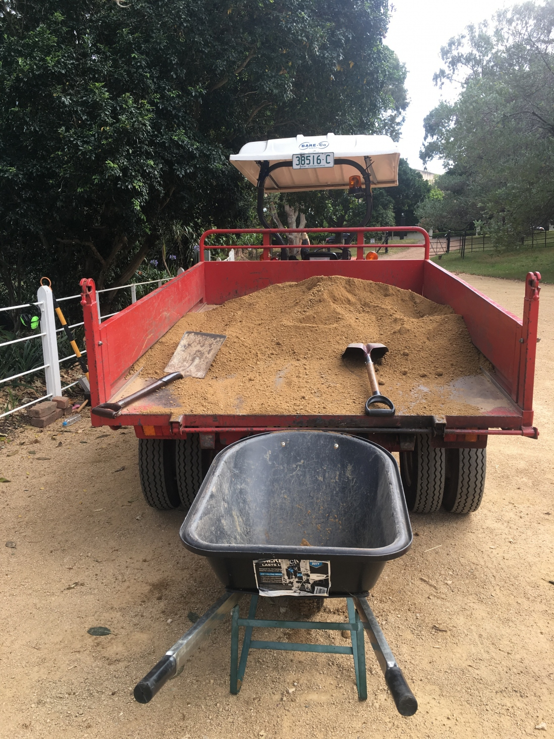 An empty wheelbarrow sits waiting to be filled with gravel from the tractor