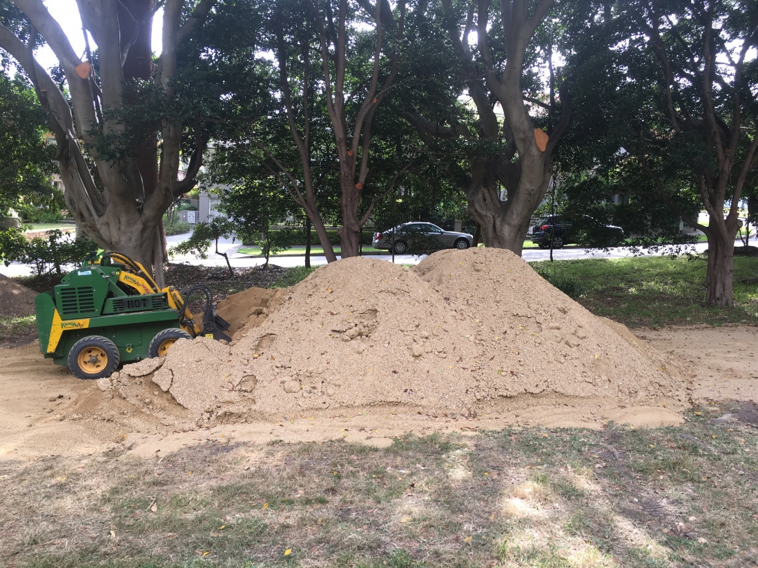 Large pile of granite ready for use on the paths with a kanga digger used for loading nearby