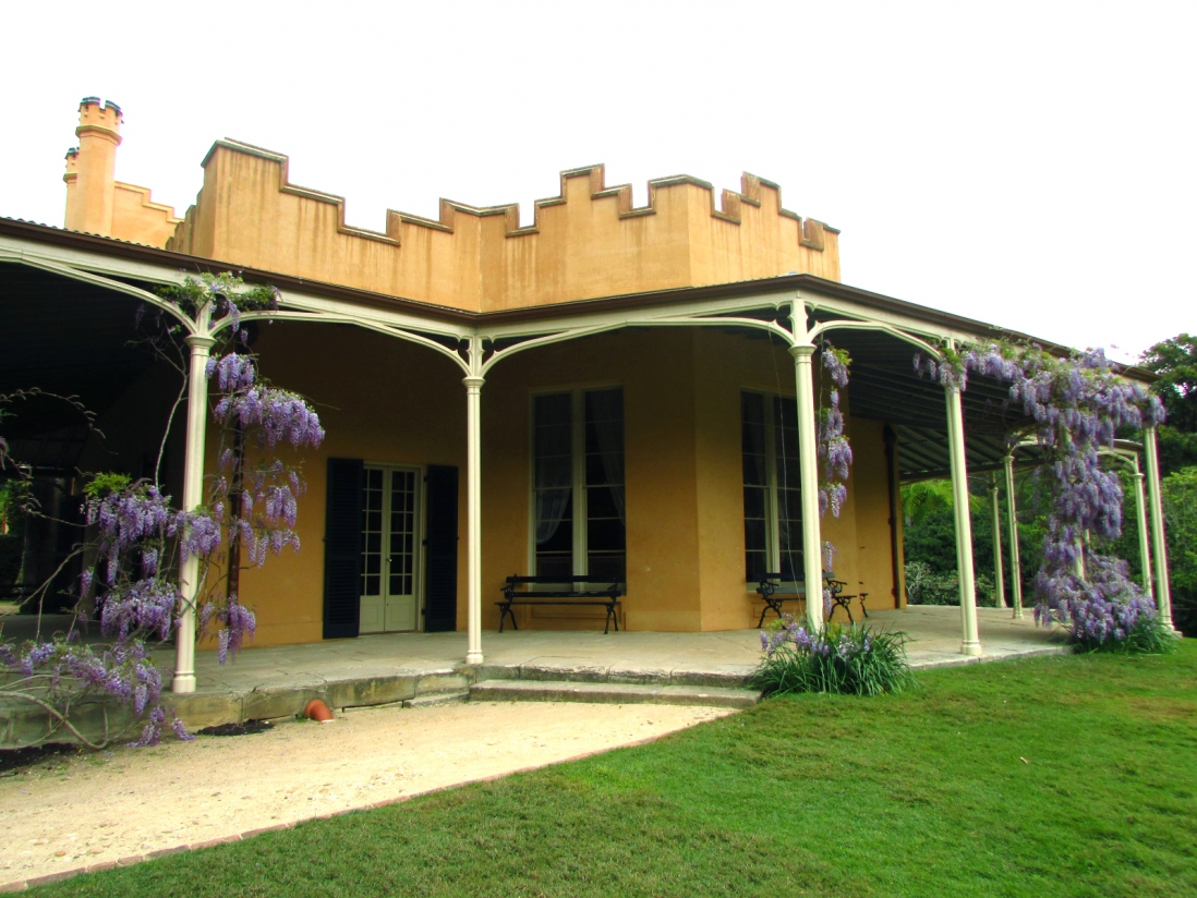 View of verandah and facade, with wisteria vines.