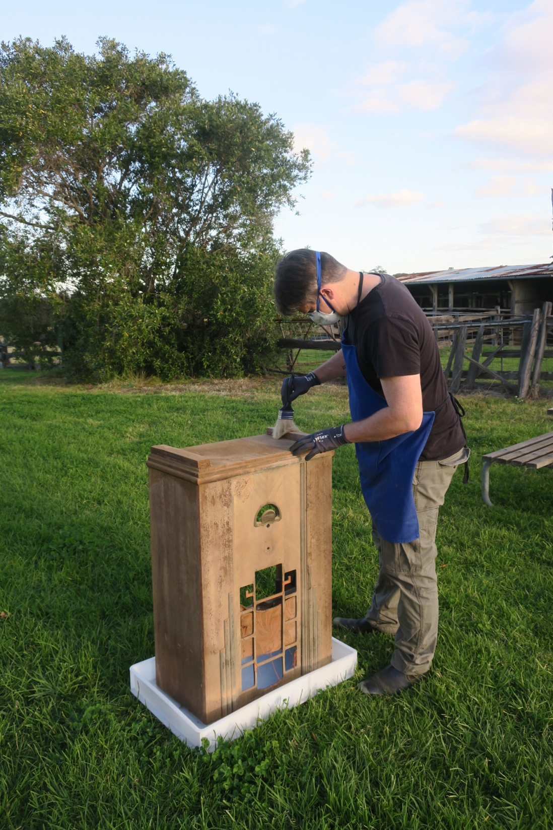 Outdoors shot of man cleaning wooden radio cabinet.