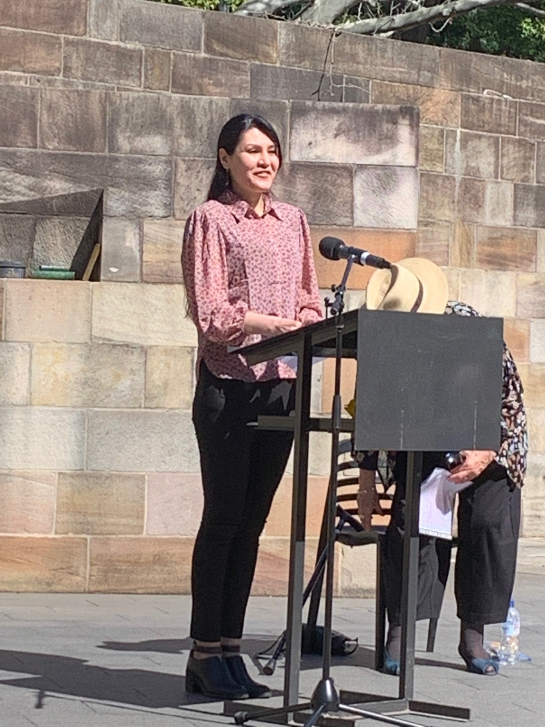 Woman speaking at outdoor podium.