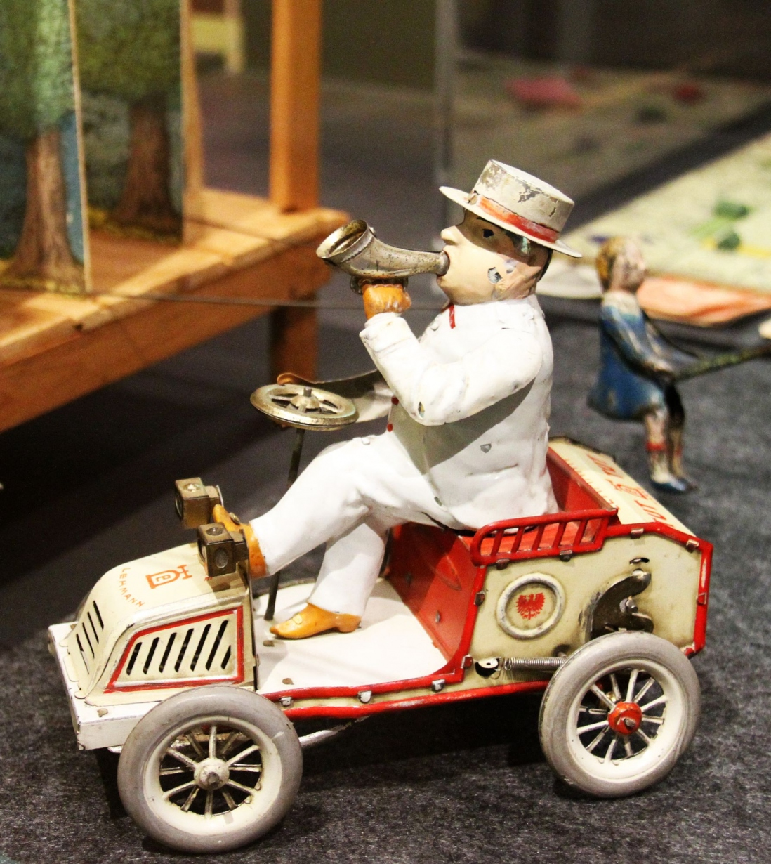 This is a photograph of an early open car with a driver blowing a trumpet