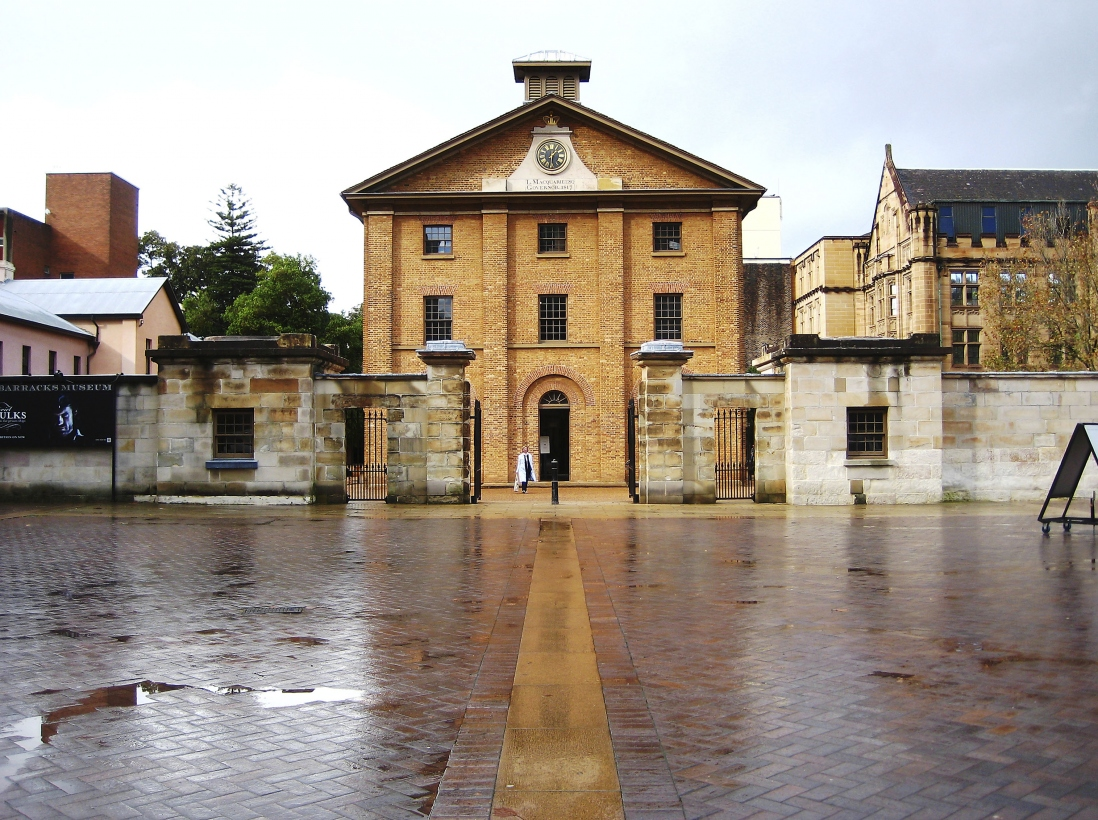 Imposing 3 storey brick building with clock set into gable end of roof, overlooking courtyard and town square. A person is walking towards the open front door of the building through the main entrance gates, past a pair of guardhouses.