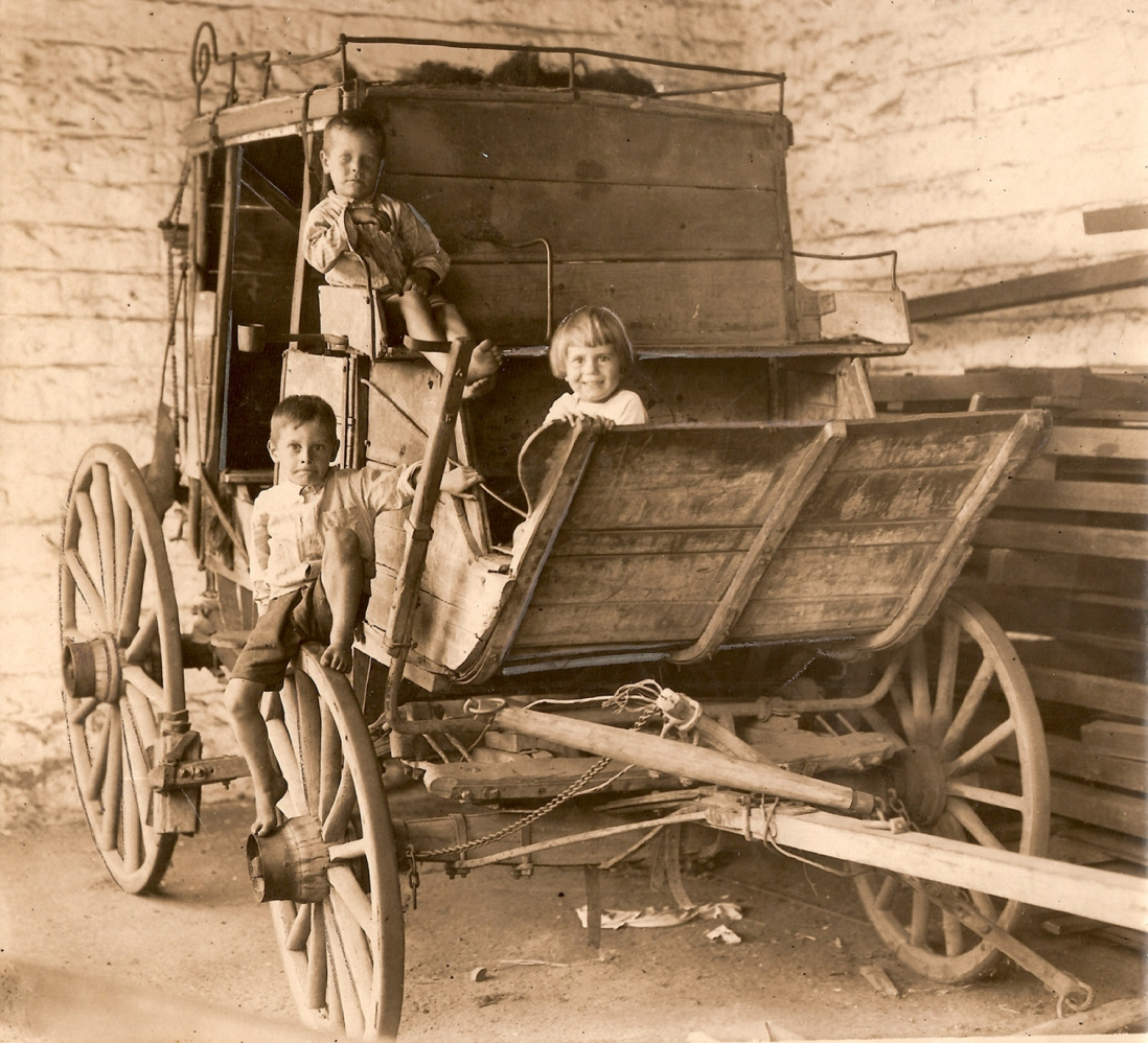 Sepia toned photograph of three children on or next to wooden coach.