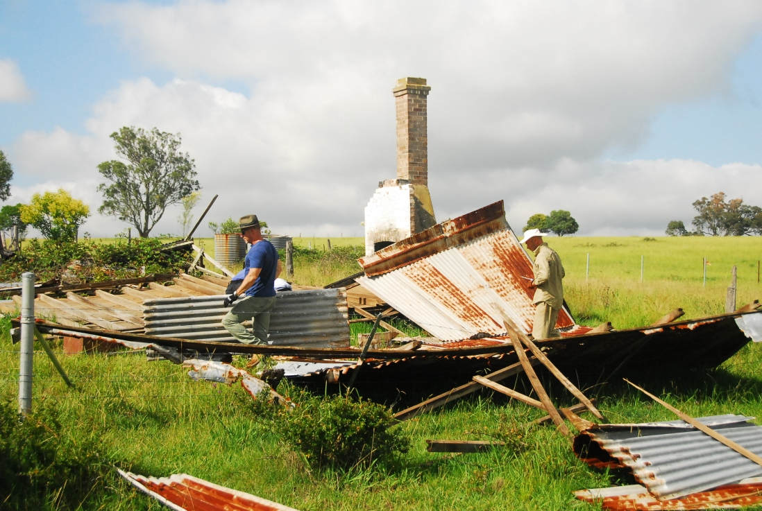 Two men remove remove corrugated iron sheets from the remains of the cottage. The old chimney can still be seen still standing in the background.
