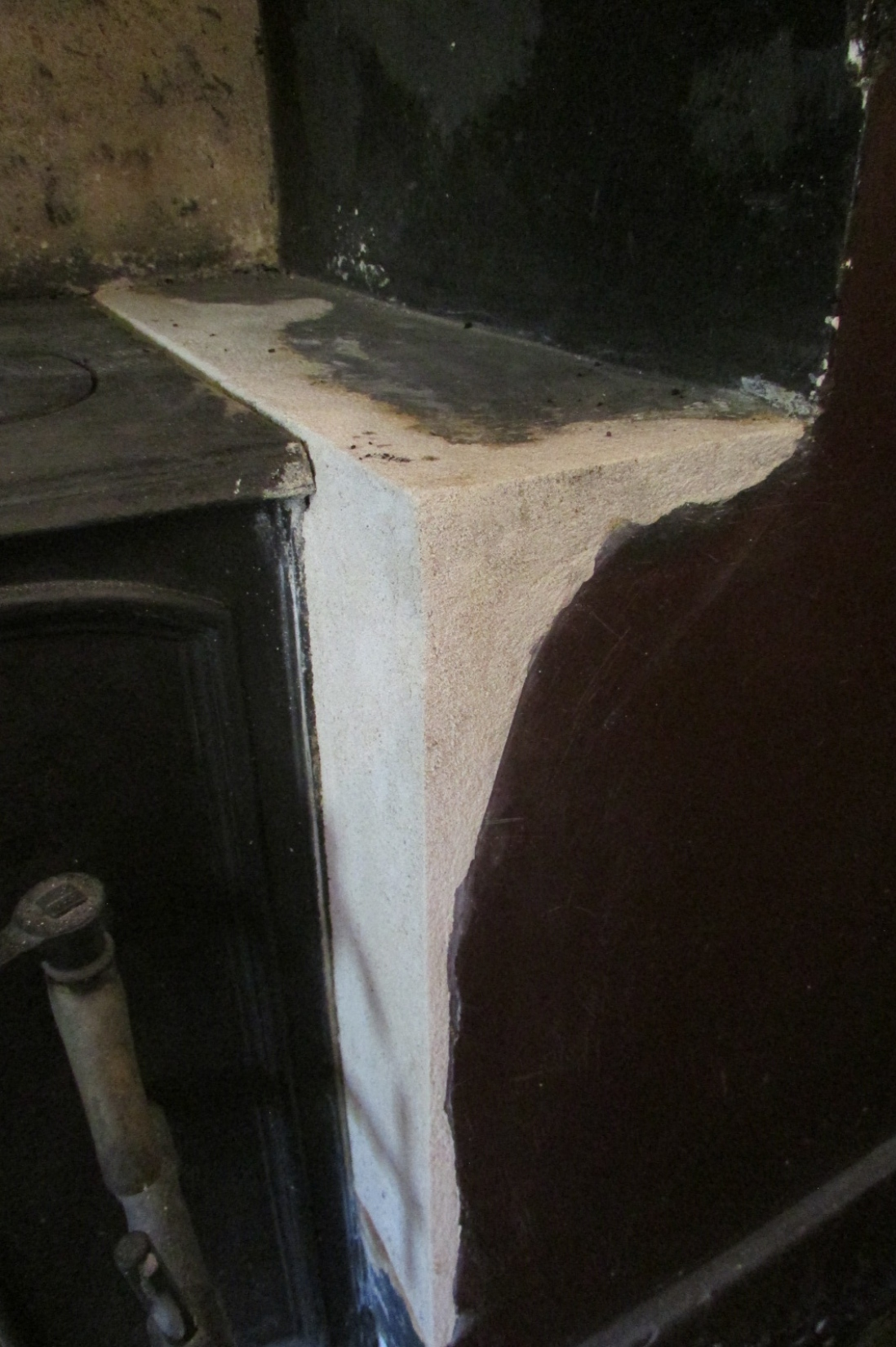 Closeup of white plaster inserted into black fireplace surround.