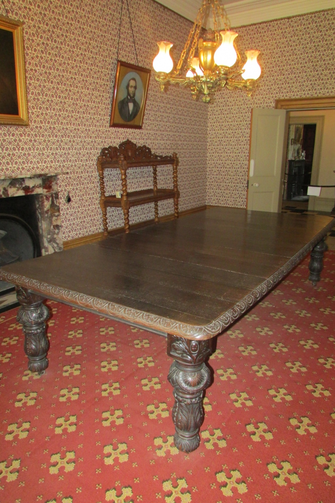Wooden table and other furniture sitting on red and gold patterned carpet.
