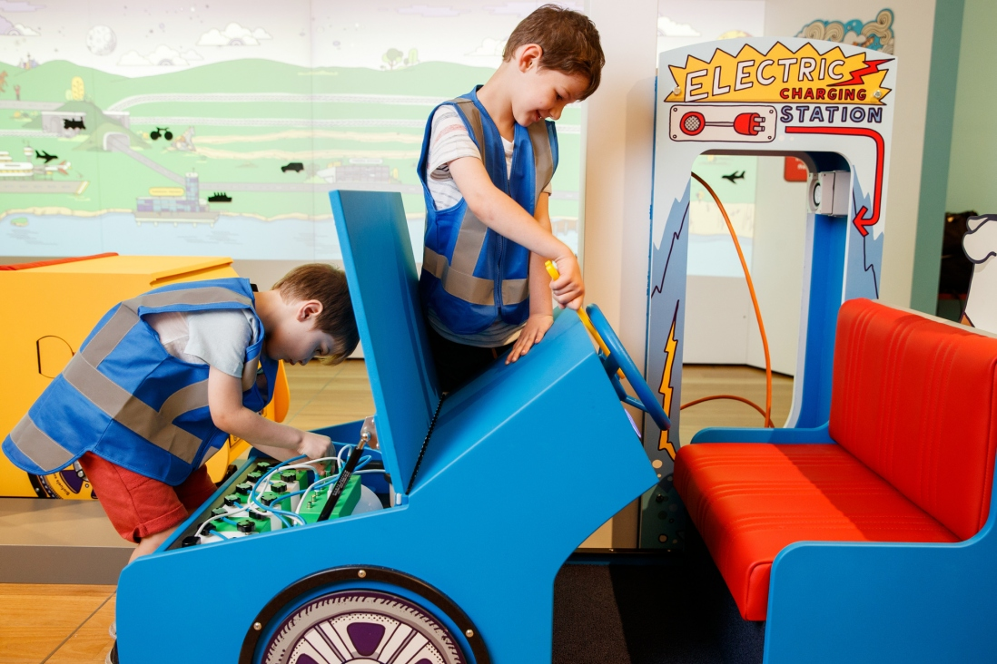 Exhibition view of two boys playing with a car