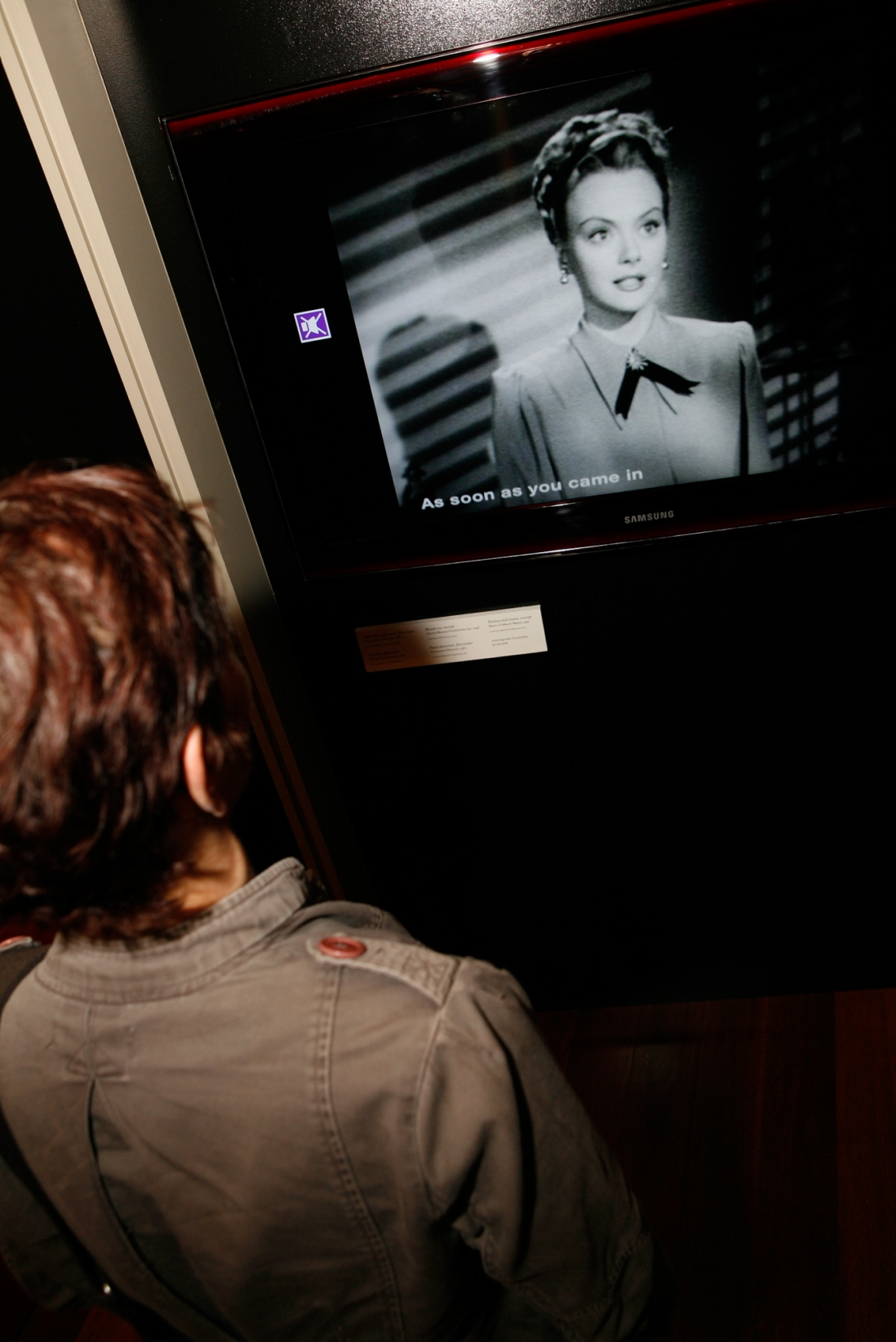 A visitor watches footage in the Femme Fatale exhibition at the Justice & Police Museum