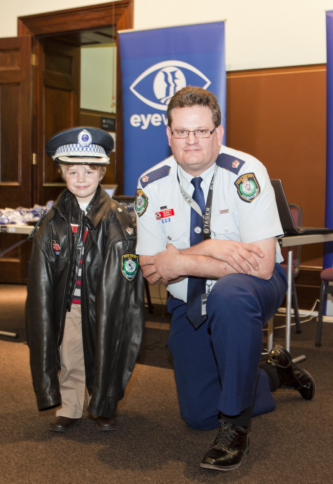 Josh Maxwell, from NSW Police Eyewatch, lends his uniform coat and hat to Stephen for a photograph in the Water Police Court at the Justice and Police Museum