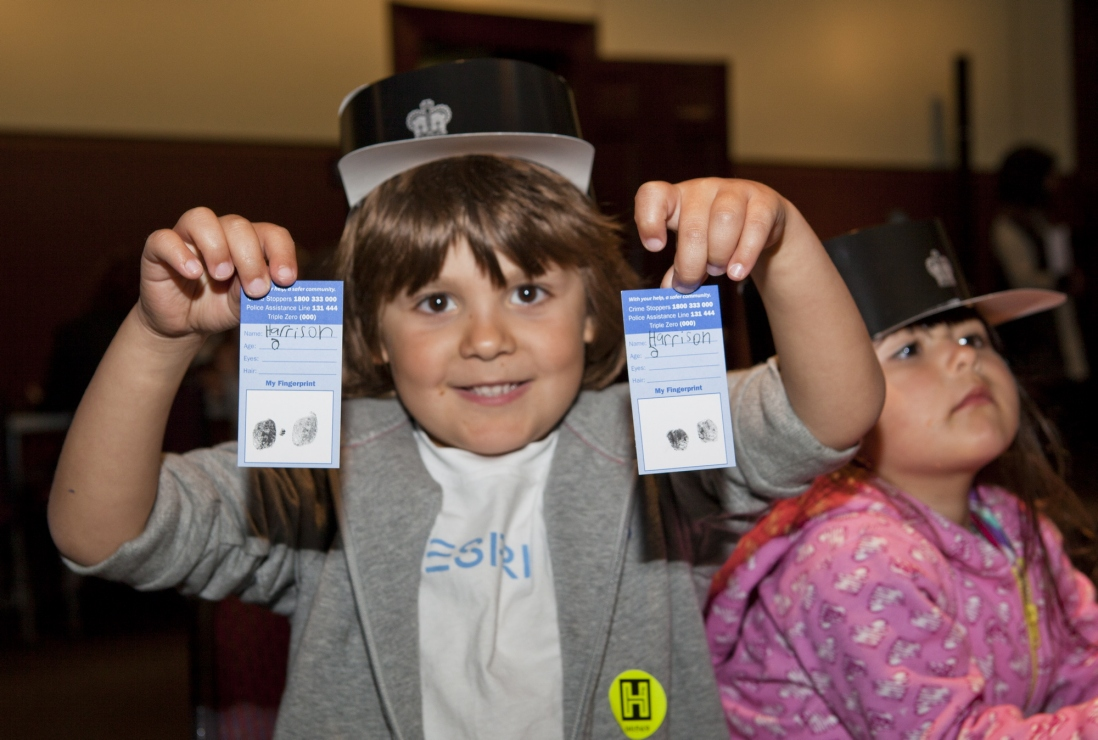 Harrison shows off his completed fingerprint cards at the fingerprinting activity in the Water Police Court, Justice and Police Museum