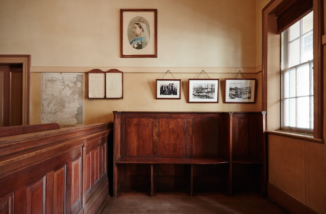 Wooden panelled counter and bench with framed photos on wall above.
