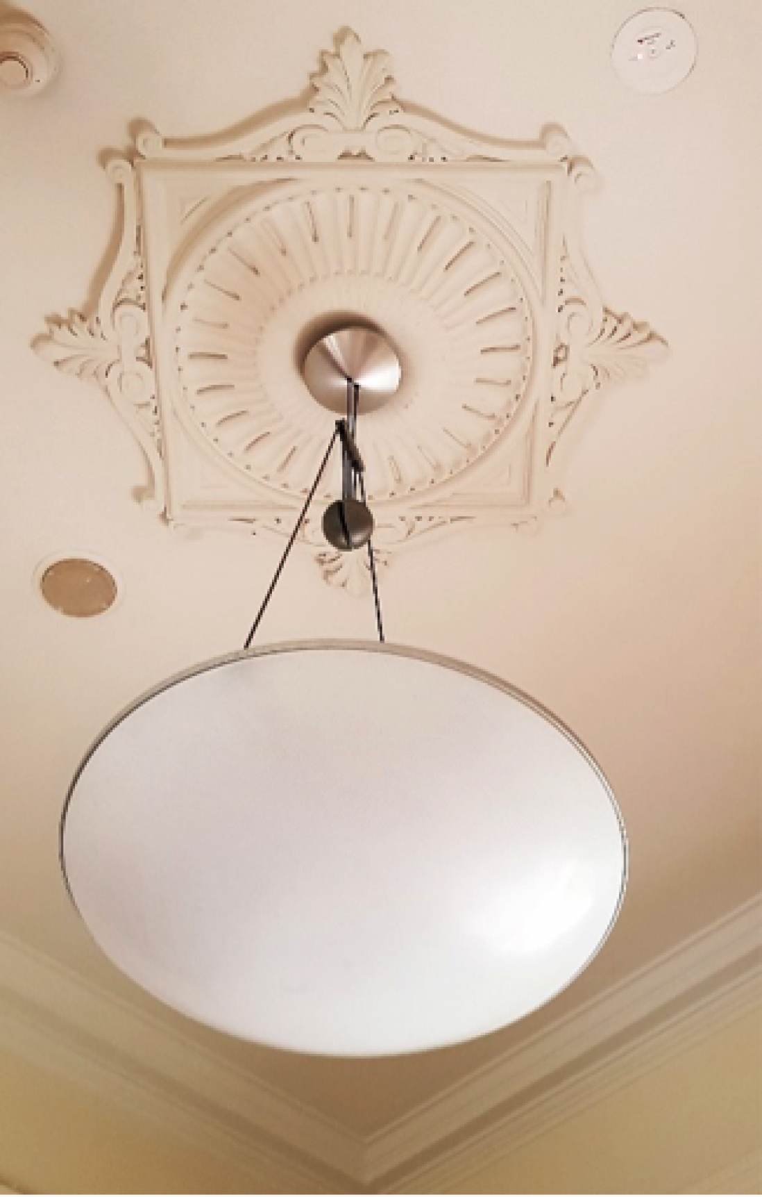 Image of the Celling rose at The mint. It features acanthus leaves in the motif and has the light fitting coming out of the centre of it.