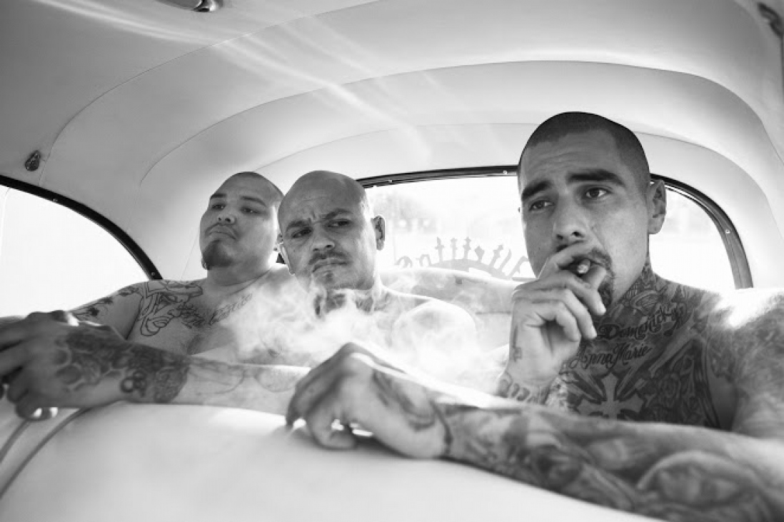 Black and white photo of three tattoo covered men in the back of a vintage car. One is smoking a cigar.