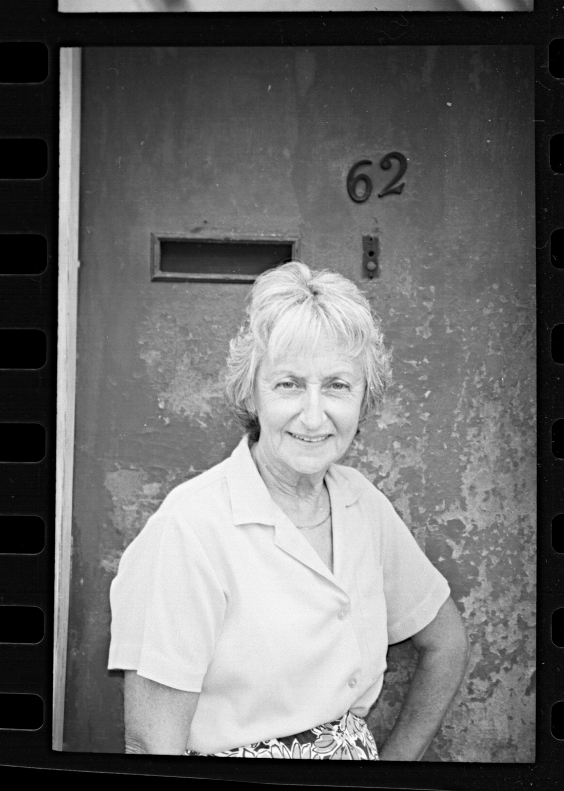 Black and white photo of woman outside doorway with the number 62 visible above her head.