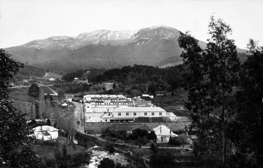 B/W photogrpah of grim looking institution in a valley underneath a large, snow covered mountain, with a river running past its perimeter walls.