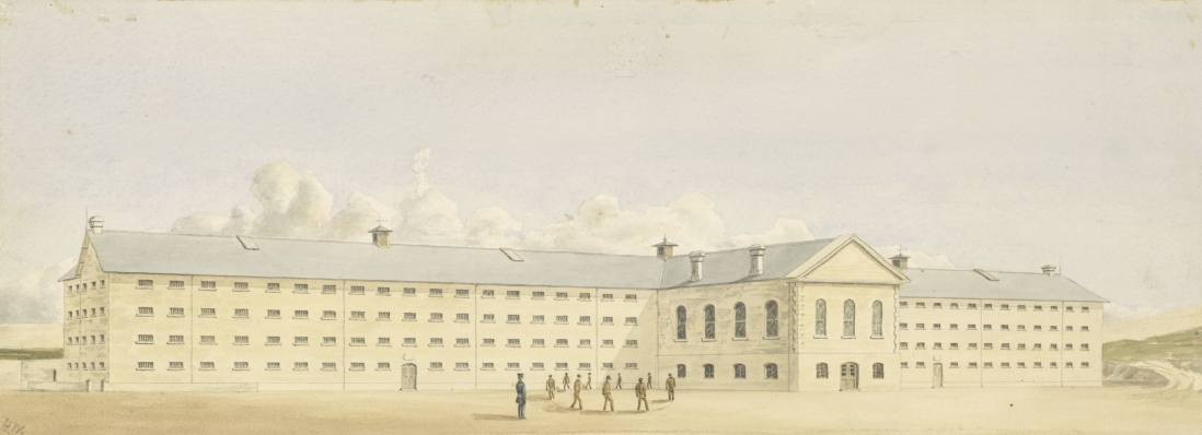 Group of male prisoners under guard walking around in a circle within the grounds of a large prison complex, with a 4 storey institutional building in the background, with cloud and blue sky above.