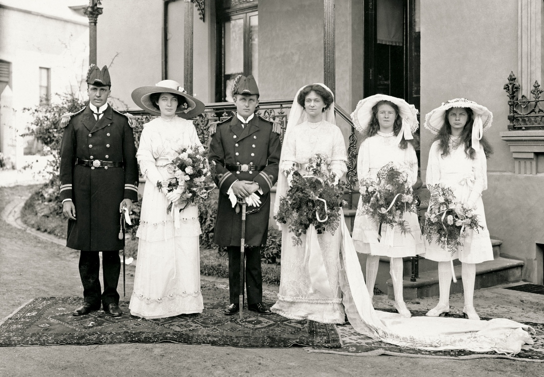 Bride and groom stand on a Persian rug laid on the drive outside a large house. A couple stand to their right and two flower girls to their left.