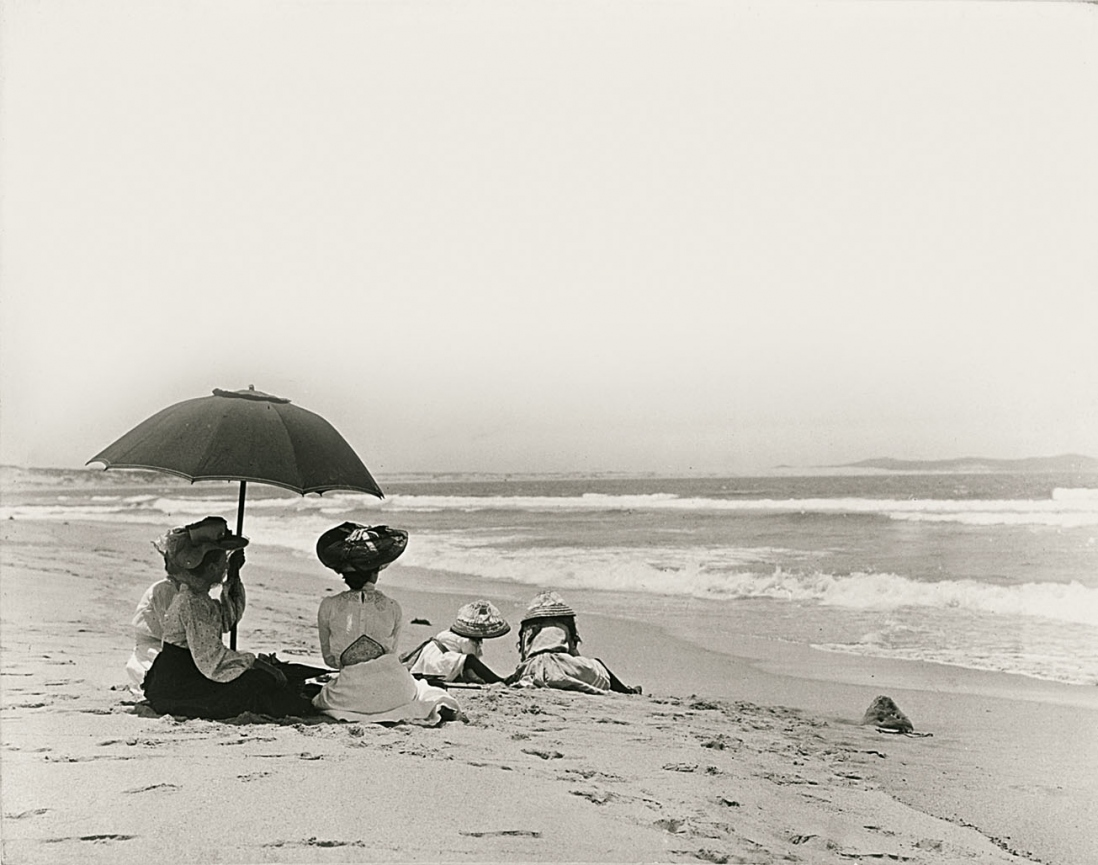 A group sit on a deserted beach. Children dig in the sand in the background while three women shelter under a large umbrella in the foreground