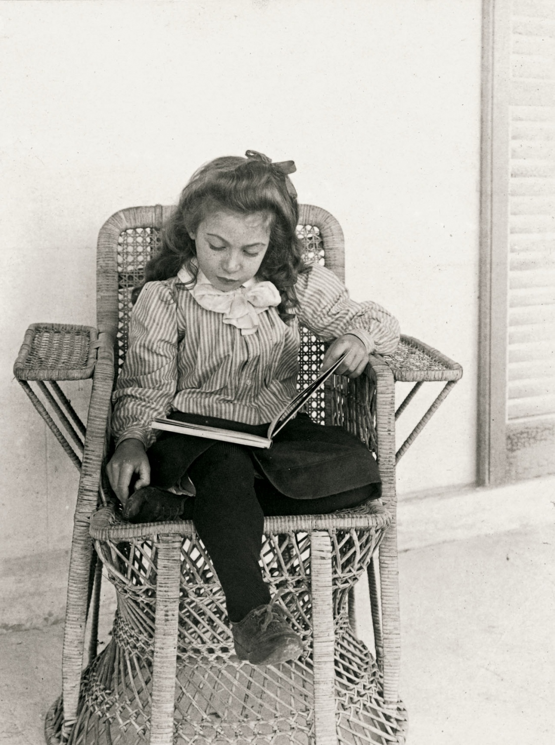 Young girl sits in a cane chair reading a book.
