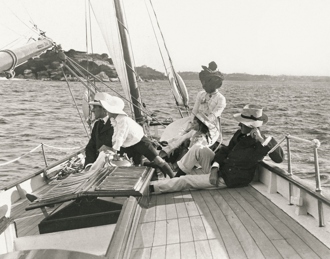 The family including a small boy are shown lying on the deck of a small wooden boat sailing on the harbour.
