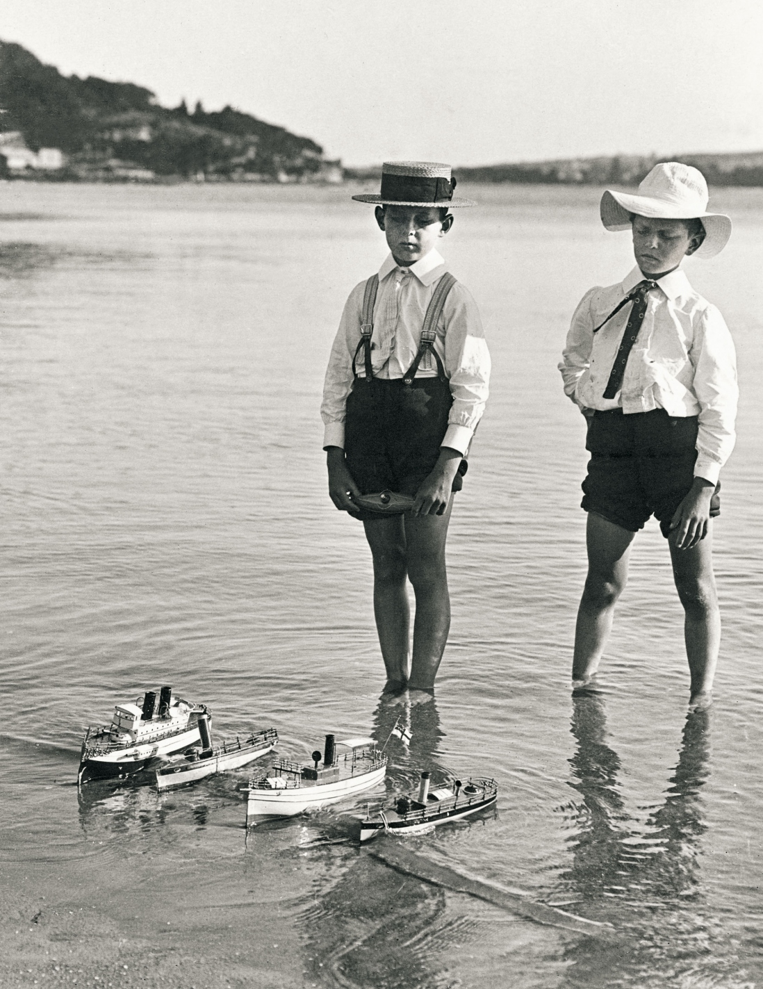 Two boys stand in shallow water wearing shorts, white shirts with tei or braces and hats. Infront of them is a row of four toy ships.