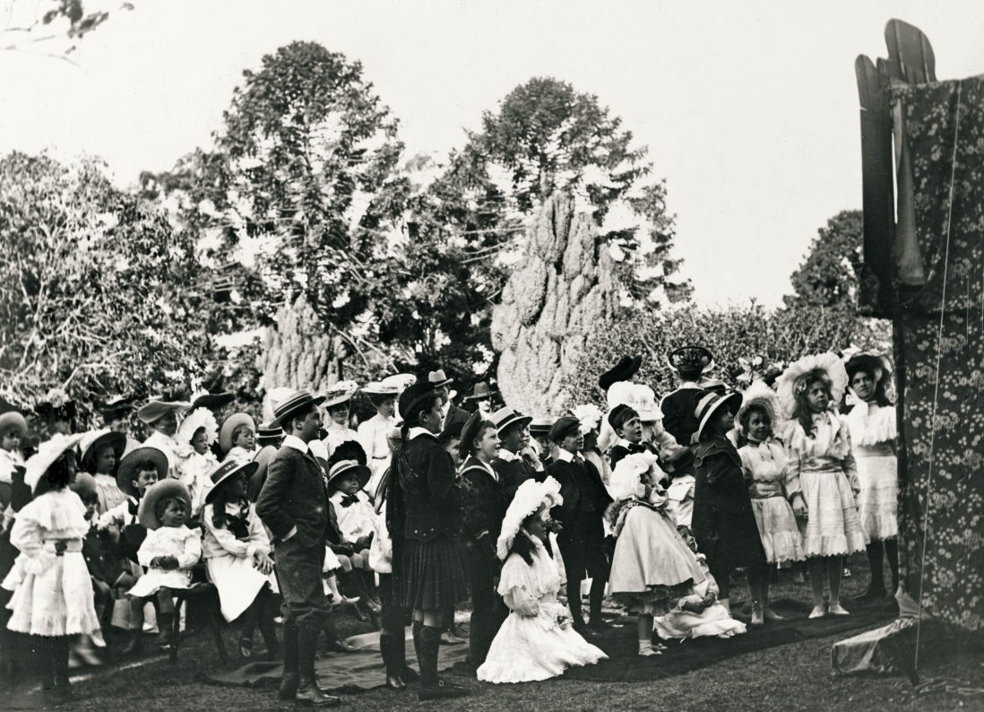 Crowds of children watch a puppet show in the elaborate garden of Yaralla.