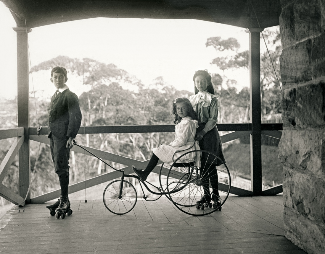 Three children on a verandah. Two children are rollerskating, one holds the handles of a three wheeled cart being ridden by his sister.