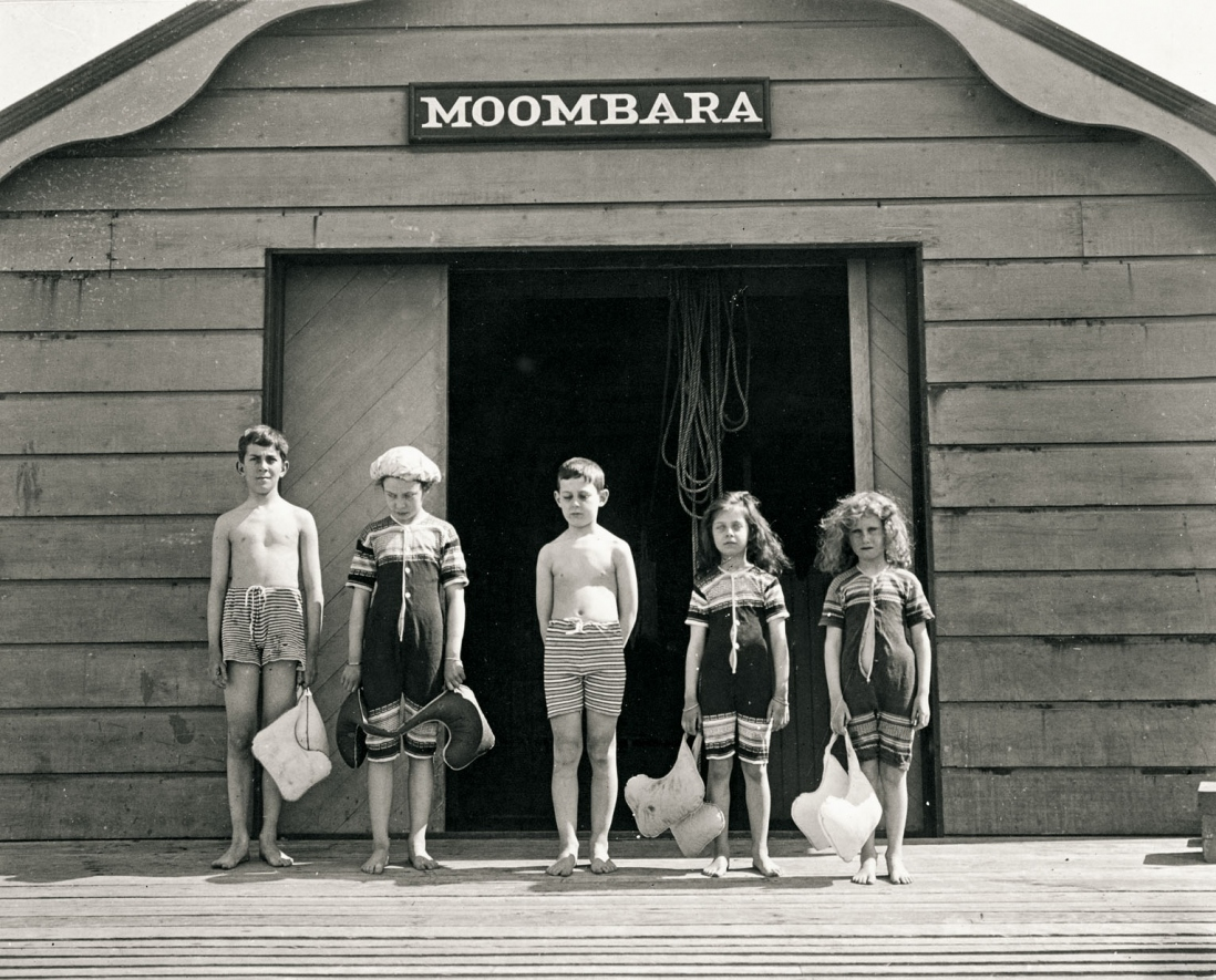 Row of five children stand in front of a timber boatshed. They wear knitted swimming costumes and carry life vests.