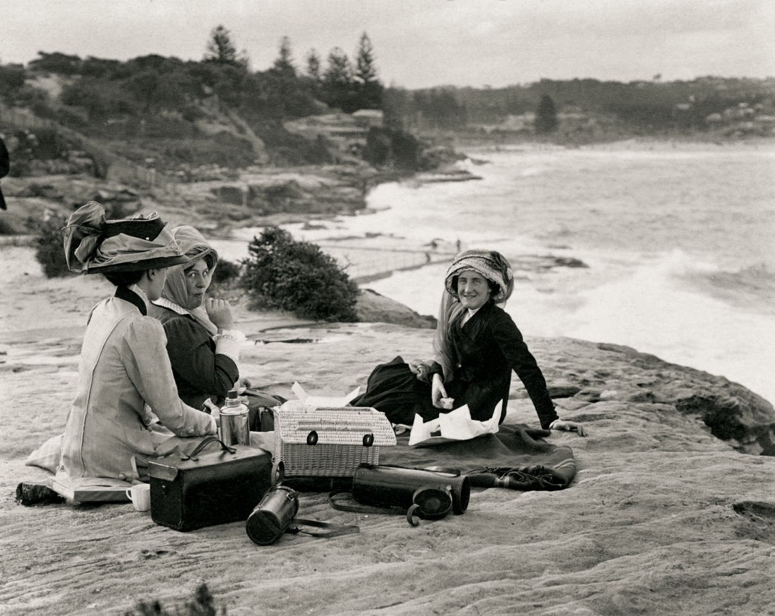 Black and white photograph of group sitting on sand. The women are wearing elaborate motoring hats with scarves.
