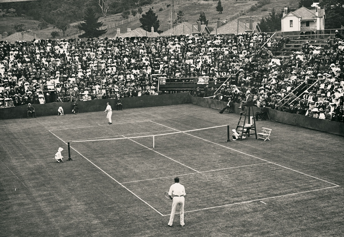 View of lawn tennis match. The male players wear white and are surrounded by crowds sitting in timber grandstands encircling the court.