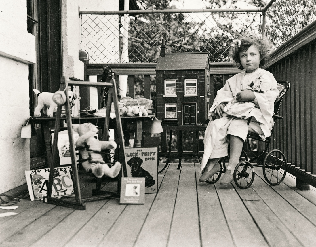Young girl sits on a chair with wheels on a verandah. She is surrounded by toys including a dolls house and fluffy toy elephant. She holds a teddy bear.