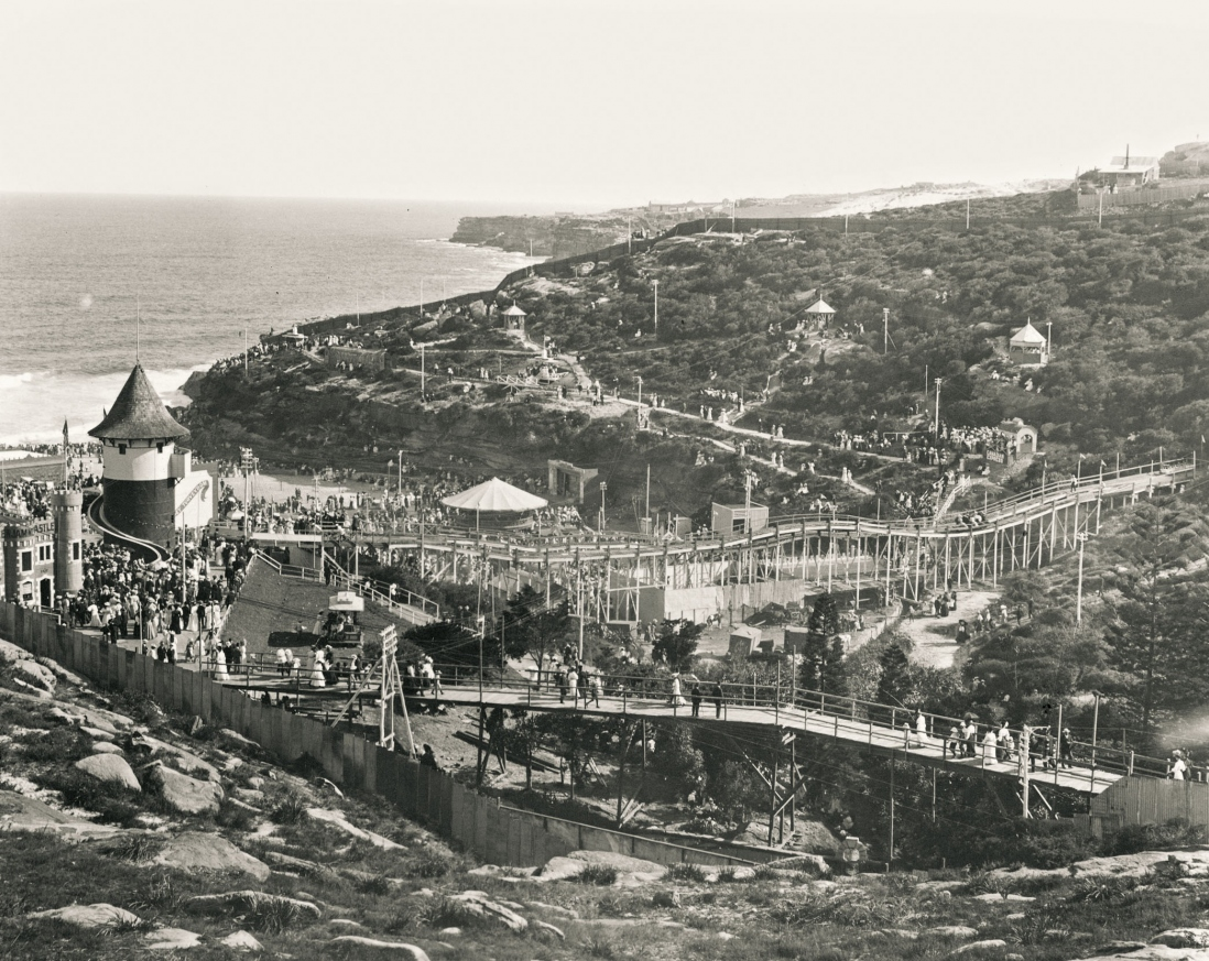 View of the roughed headlands and steep hills leading to Tamarama Beach crowded with people and light with timber walkways and amusement park structures.